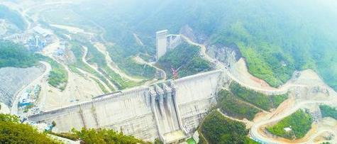 """上存水库大坝正在进行最后的封顶施工,近30层楼高的坝体横亘山谷,一旦建成蓄水,将呈现""""高峡出平湖""""的美景"""