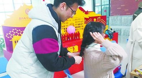 厦门大学翔安校区,一名男生为女生编麻花辫。(厦大药学院研究生会供图)