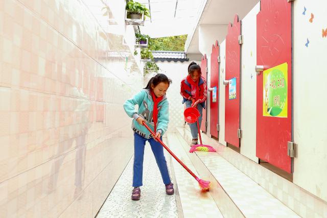 两名学生在贵州省织金县熊家场镇小学的厕所打扫卫生(2018年10月23日摄)。