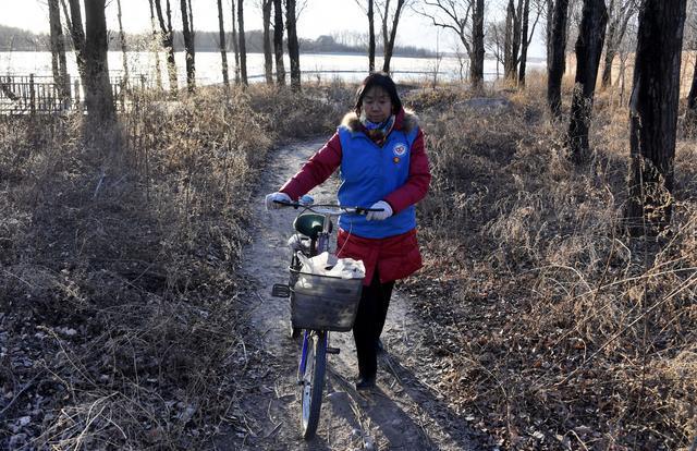 贺玉凤推着自行车赶往妫河边拾捡垃圾
