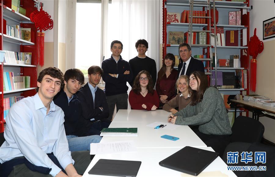 3月18日,意大利罗马国立住读学校校长雷亚莱(后排右一)与写信的学生们在一起。新华社记者 程婷婷 摄