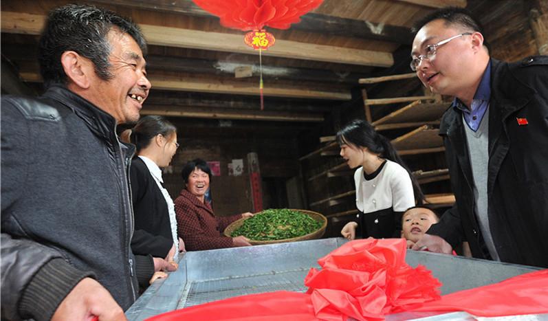 福鼎市管阳镇广化村贫困户茶农老汪(左)收到党员干部送来的茶叶萎凋机,十分激动。福鼎市建立党员干部一对一帮扶机制,帮助贫困户发展生产。