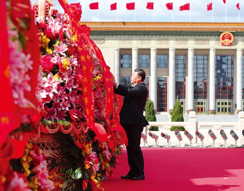 2018年9月30日上午,黨和國家領導人習近平、李克強、栗戰書、汪洋、王滬寧、趙樂際、韓正、王岐山等來到北京天安門廣場,出席烈士紀念日向人民英雄敬獻花籃儀式。這是習近平整理花籃上的緞帶。 新華社記者 謝環馳/攝