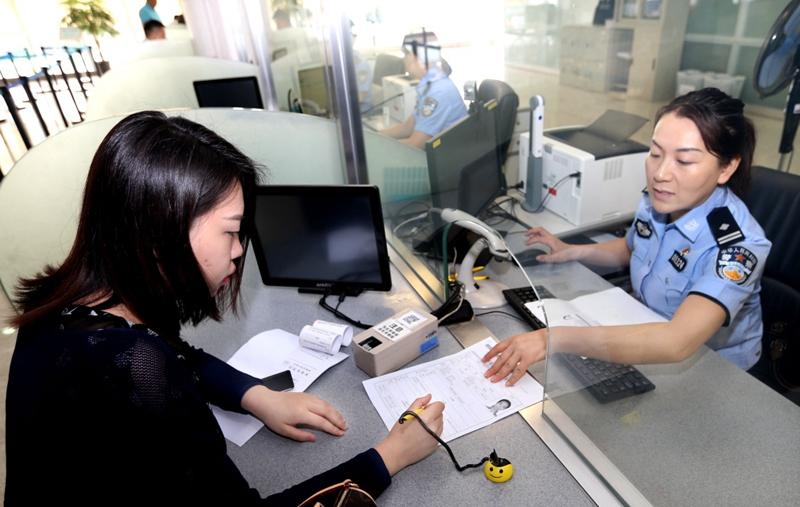 市民窦月雯在上海市公安局出入境管理局的网约专窗办理证件(2018年5月31日摄)。新华社记者 凡军 摄