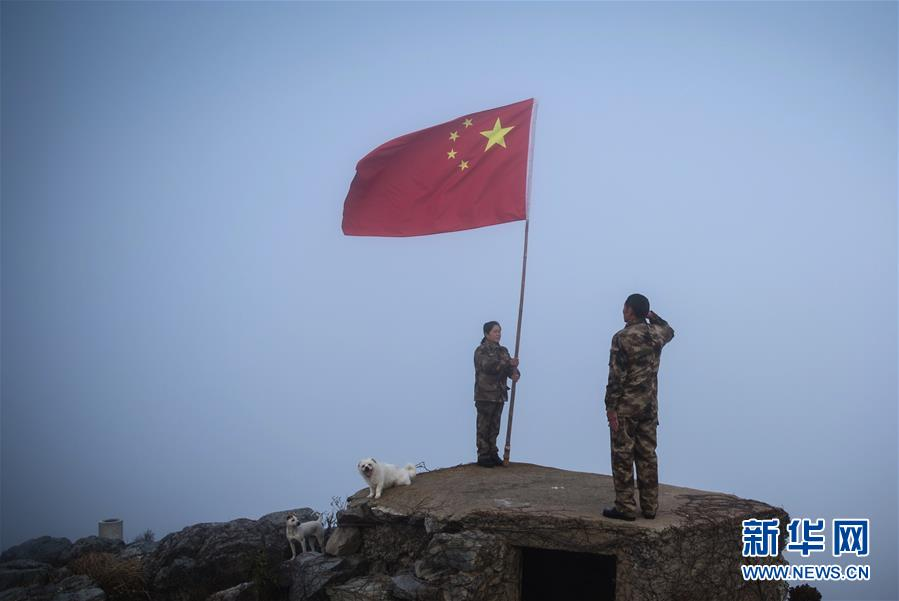 王继才夫妇在江苏开山岛的最东边举行向国旗敬礼仪式(2017年1月1日摄)。新华社记者 李响 摄