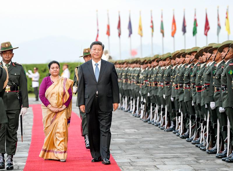 10月12日,国家主席习近平乘专机抵达加德满都,开始对尼泊尔进行国事访问。尼泊尔总统班达里在机场为习近平举行具有浓郁尼泊尔民族特色的欢迎仪式。这是习近平在班达里陪同下检阅仪仗队。新华社记者 李学仁 摄