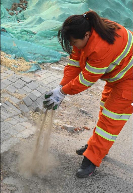 圖為李萌用沙土掩蓋抽糞車作業時灑漏在街邊的糞水,以減少氣味