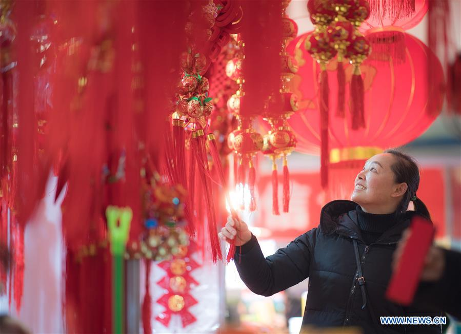 A resident selects goods at a shopping fair held to greet the upcoming Spring Festival at Wuhan International Conference & Exhibition Center in Wuhan, capital of central China