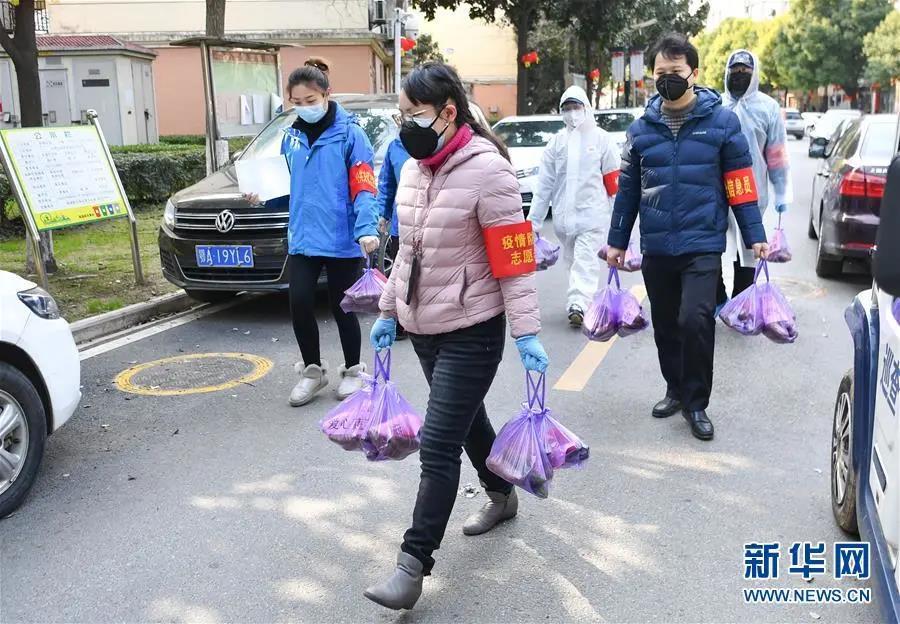 武汉市武昌区华锦社区的志愿者在为社区居民送菜上门(2月23日摄)。新华社记者 程敏 摄