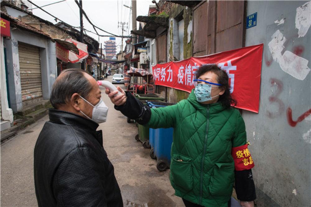 武汉西城壕社区网格员曹岚英(右)为居民测量体温(2月7日摄)。新华社记者 肖艺九 摄