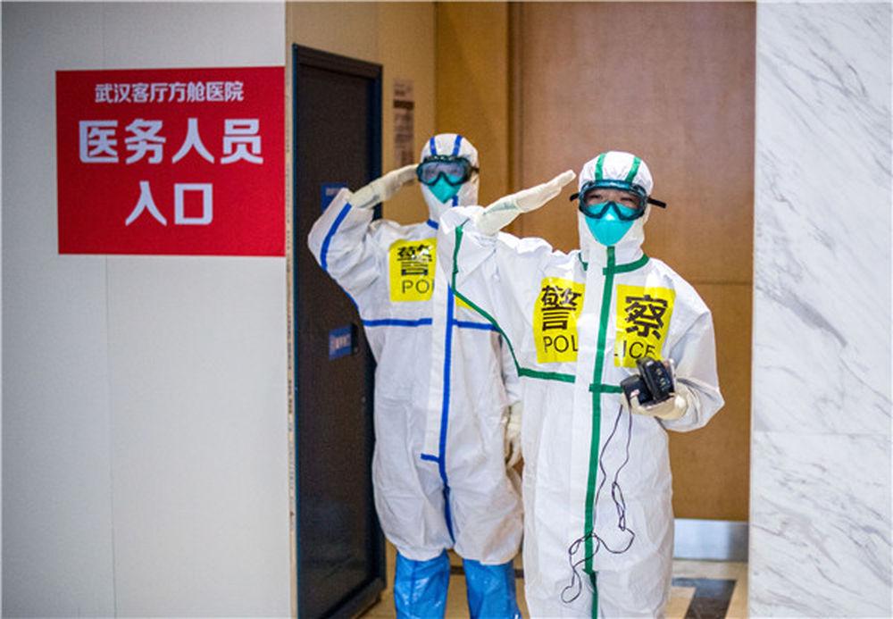 在武汉客厅方舱医院,来自武汉市东西湖区公安分局的民警张锦星(右)与同事刘晨在进方舱前向同事敬礼(2月25日摄)。新华社记者 肖艺九 摄