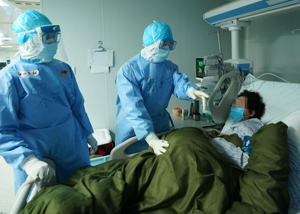 在武汉火神山医院,重症医学一科主任张西京(中)、副主任宋立强在查房(3月17日摄)。新华社记者 王毓国 摄