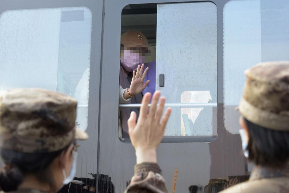 在武汉火神山医院,治愈患者与医疗队队员挥手道别(2月13日摄)。新华社发(范显海 摄)