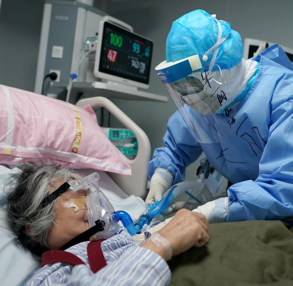 武汉火神山医院重症医学一科80后护士朱丽为患者调整管线(3月20日摄)。新华社记者 王毓国 摄