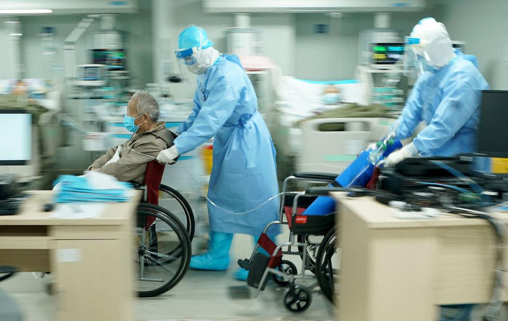 3月20日,武汉火神山医院重症医学一科副主任宋立强(中)护送81岁新冠肺炎重症患者去做CT检查。新华社记者 王毓国 摄