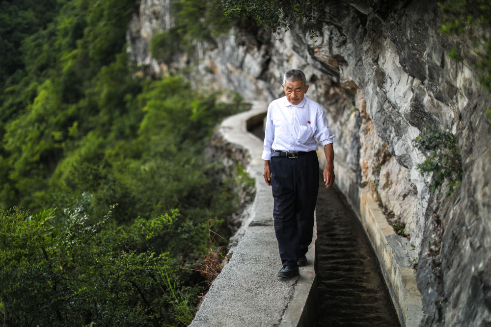 """贵州遵义播州区团结村老支书黄大发沿着修建在绝壁上的""""大发渠""""巡查(2018年8月11日摄)。新华社记者 刘续 摄"""