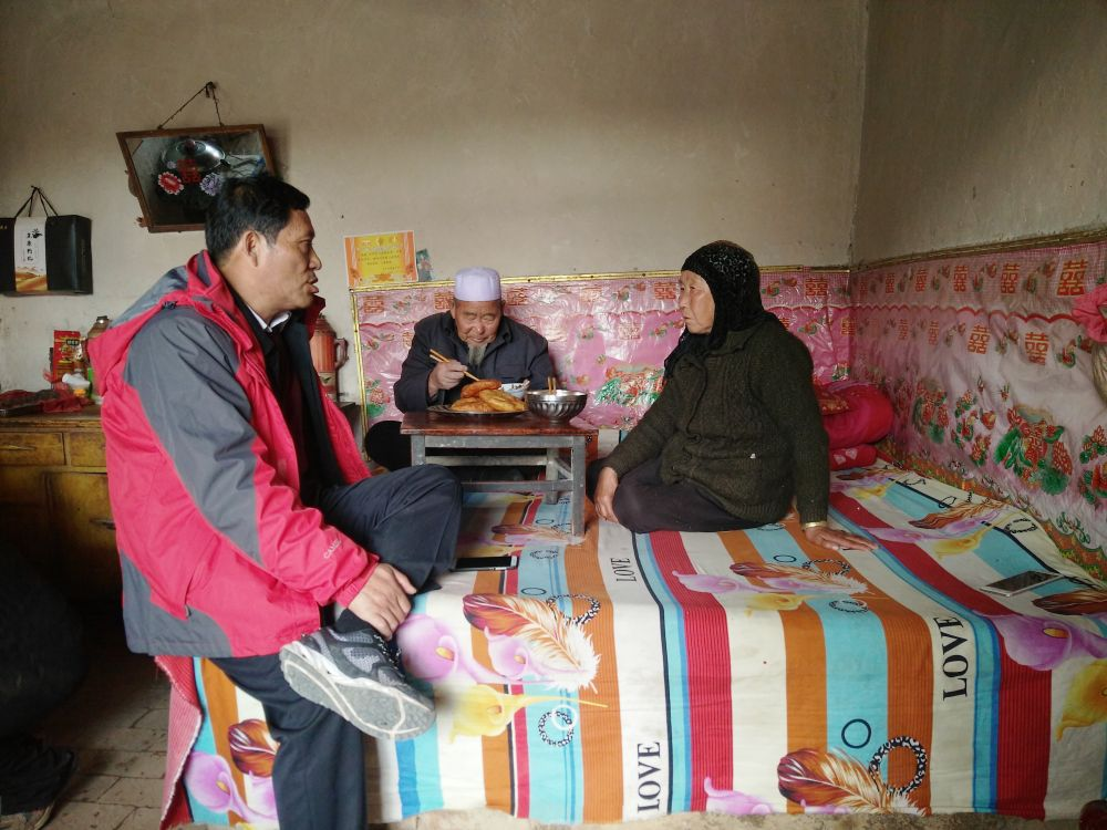 宁夏西吉县涵江村第一书记秦振邦(左)在建档立卡贫困户马维仓家了解情况并宣讲扶贫政策(资料照片)。新华社发
