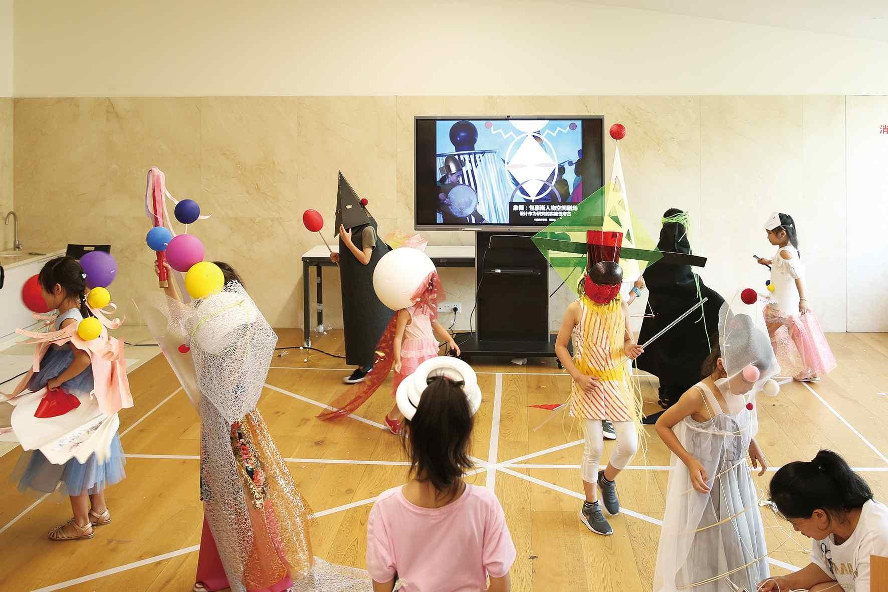 """在中國美術學院美術館舉辦的""""包豪斯人物空間劇場兒童工坊""""公教活動上,孩子們展示自己做的服裝。"""