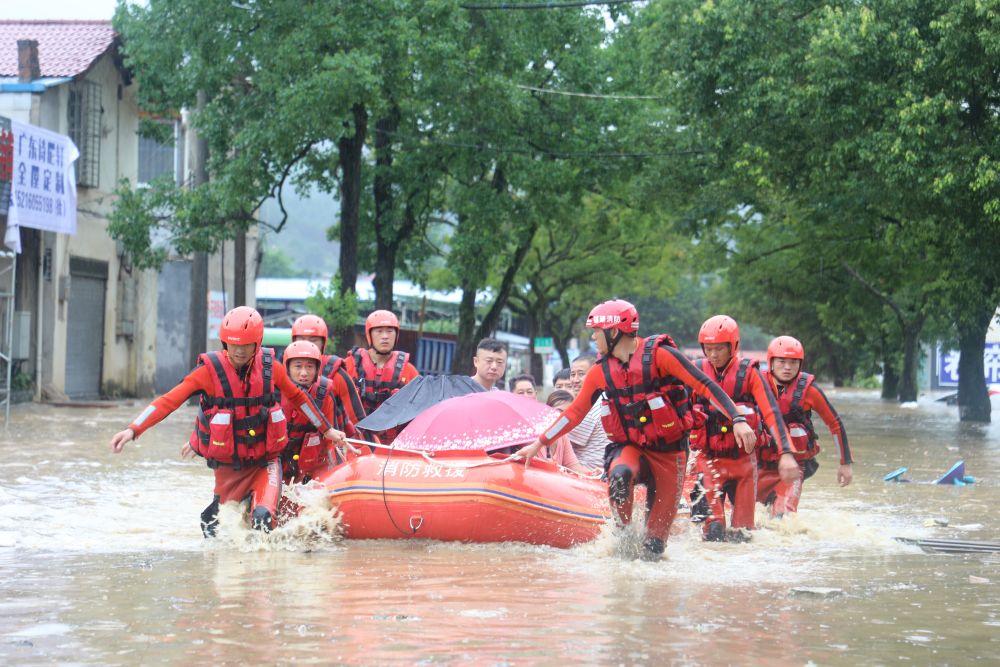 △2020年7月9日,在福建南平武夷山市崇安街道石雄社區,消防人員轉移被洪水圍困群眾。