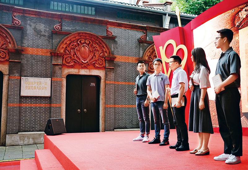 """2020年6月29日,""""新時代答卷人——上海市教育系統慶祝中國共產黨成立99周年暨學生愛國主義教育主題活動""""在中共一大會址前舉行。來自復旦大學、同濟大學、上海建橋學院、上海市曹楊第二中學等8所學校的200余名師生代表參加活動,通過情景講述、現場教學、集體朗誦等形式,慶祝中國共產黨成立99周年,展現廣大上海學子的愛國情、強國志。圖為復旦大學師生代表在一大會址前展示情景教學。 新華社記者 劉穎/攝"""