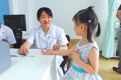 图为郑州市中医院儿科专家王晓燕在北京市丰台区妇幼保健院坐诊