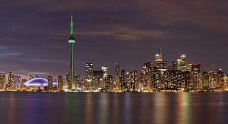 这是从多伦多湖心岛拍摄的点亮绿色灯的加拿大国家电视塔(4月22日摄).
