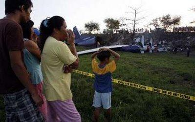 Filipino villagers look at the wreckage of a Russian cargo plane Antonov 12BP, operated by Pacific East Asia Cargo Airline, that crashed in a rice paddy in Mexico, Pampanga in northern Philippines April 22, 2010. Three crew members survived, while three others were killed in the crash, according to police investigators. REUTERS/Erik de Castro