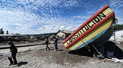 Local residents walk by a boat grounded by the earthquake and the ensuing tsunami in the fishing village of Constitucion, central Chile. (AFP/Martin Bernetti)