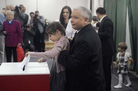 Candidate Jaroslaw Kaczynski, twin brother of the late President Lech Kaczynski, who was killed in a plane crash in Russia, lifts his brother's granddaughter Eva to cast his vote in the presidential election in Warsaw on Sunday, June 20, 2010. Poles are voting Sunday to choose Lech Kaczynski's successor. (AP Photo/Alik Keplicz)