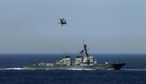 A U.S. Navy helicopter flies over a U.S. warship as they participate in joint military exercises between the U.S. and South Korea in waters off the east coast of the Korean peninsula, July 26, 2010.(Xinhua/Reuters Photo)