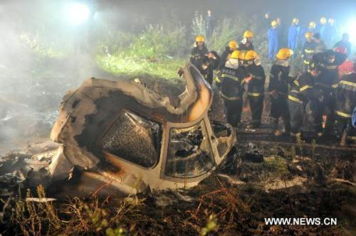 Rescuers search for survivors at the site where a passenger plane crashed in Yichun City, northeast China's Heilongjiang Province, early on Aug. 25, 2010. A passenger plane with 96 people on board crashed late Tuesday night the Yichun airport. At least 42 people were confirmed dead while the remaining 54 have been rescued and sent to hospitals.(Xinhua Photo)