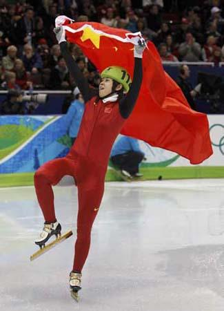 Wang Meng of China holds a national flag as she celebrates her gold medal in the women's 500 metres short track speed skating event during the Vancouver 2010 Winter Olympics, February 17, 2010. [Photo/Agencies]