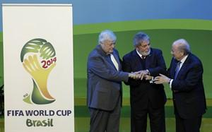 Brazilian President Luiz Inacio Lula da Silva, center, shakes hands with FIFA President Joseph Blatter, right, and Ricardo Teixeira, President of the Brazil 2014 Organising Committee, left, during the official unveiling of the emblem for the Road to Brazil 2014 Soccer World Cup at the Sandton Convention Centre in Johannesburg, South Africa, Thursday July 8, 2010.(AP Photo/Themba Hadebe)