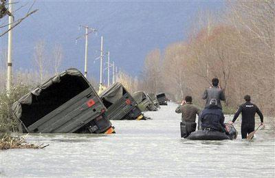Albanian army rescuers and villagers pass by a convoy of trucks pushed to the side of the road by flood water on the outskirts of Bacallek, near the city of Shkodra, Sunday, Jan. 10, 2010. (AP Photo/Hektor Pustina)