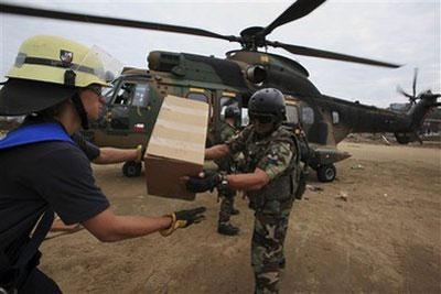 Troops and firefighters unload aid from a military helicopter in Dichato, Chile, Wednesday, March 3, 2010. (AP Photo/Ricardo Mazalan)