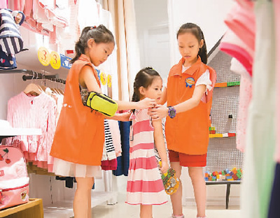 """今年8月16日,在重庆百货北碚商场,当地小学生参与""""小小搭配师""""职业体验活动,为一名小顾客试装。秦廷富摄(人民视觉)"""