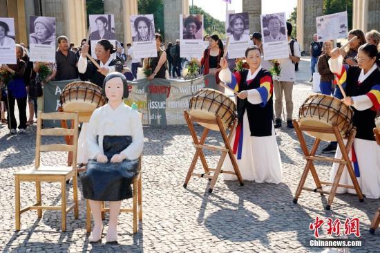 """资料图片:8月14日,在德的韩国和日本民间团体于第七个世界""""慰安妇""""纪念日之际在柏林勃兰登堡门前举行集会,一座""""和平少女像""""出现在当天的活动现场。中新社记者 彭大伟 摄"""