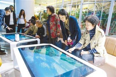 """在辽宁省大年夜连市某购物中间的""""沉浸式数字旅游体验中间"""",人们在体验AI智能触控台等旅游新产品。人夷易近视觉"""