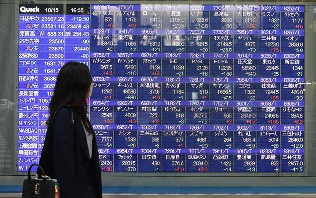 10月15日,行人经过日本东京街头一处电子股指显示屏。新华社