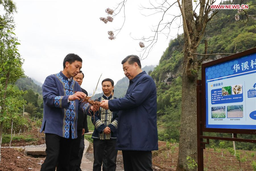 Chinese President Xi Jinping, also general secretary of the Communist Party of China Central Committee and chairman of the Central Military Commission, talks with a villager to learn about the progress of poverty alleviation and in solving prominent problems including meeting the basic need of food and clothing and guaranteeing compulsory education, basic medical care and safe housing, in Huaxi Village of Shizhu Tujia Autonomous County, southwest China