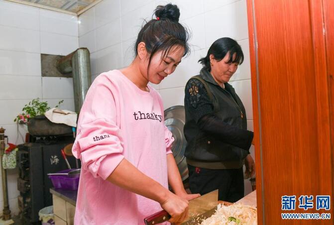 4月17日,内蒙古兴安盟科尔沁右翼中旗巴彦敖包嘎查的傣族媳妇杨丽(左)和婆婆一起做晚饭。新华社记者 彭源 摄
