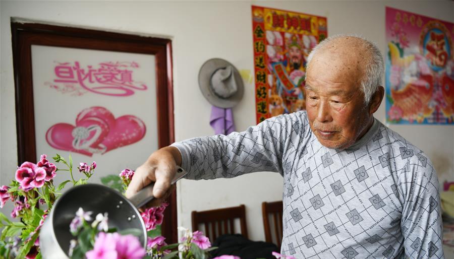 元宝村村民罗庆宝在家中浇花