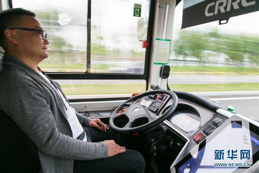一辆无人驾驶公交车在国家智能网联汽车(长沙)测试区内行驶,驾驶座位的测试员关注路况和驾驶数据(4月28日摄)。 新华社发(陈思汗摄)