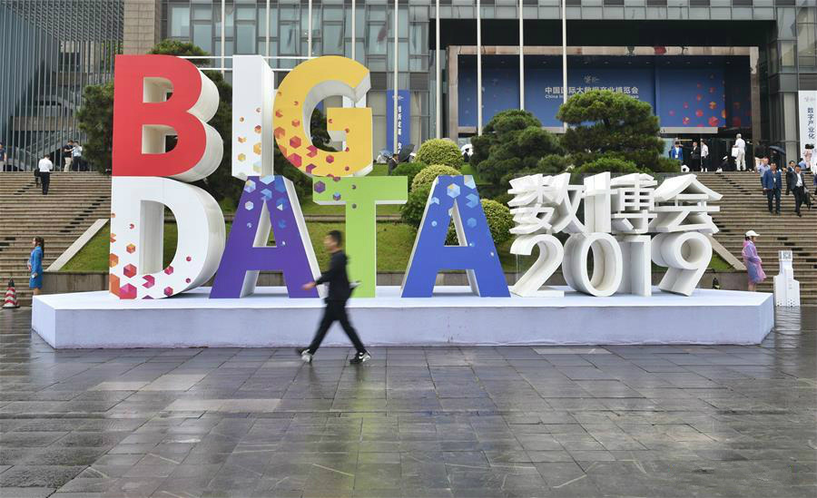 A visitor walks past a sign of China International Big Data Industry Expo 2019 in Guiyang, southwest China