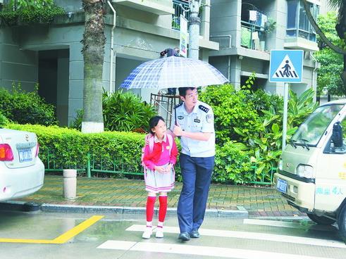 小區警察雨天護送小區兒童安全返家。