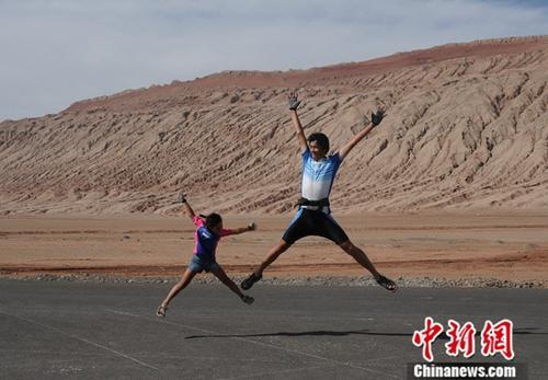 2009年9月,到达古丝绸之路骑行的终点火焰山,父女俩跳跃欢呼。中新社发 陈守忠 供图