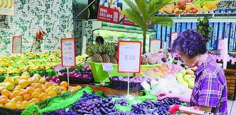 今年夏天水果种类十分丰富,市民正在挑选水果。