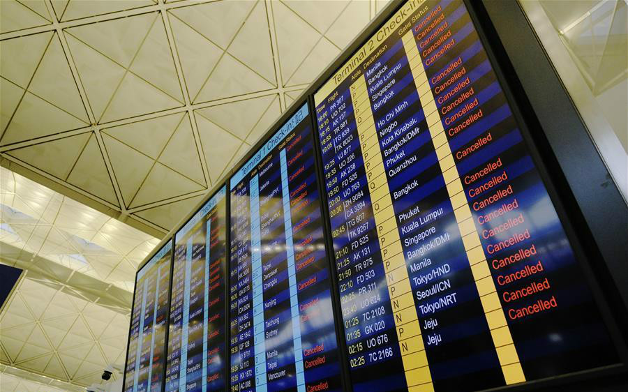 Cancelled flights are shown on a screen at Hong Kong International Airport in Hong Kong, south China, Aug. 12, 2019. All flights in and out of China