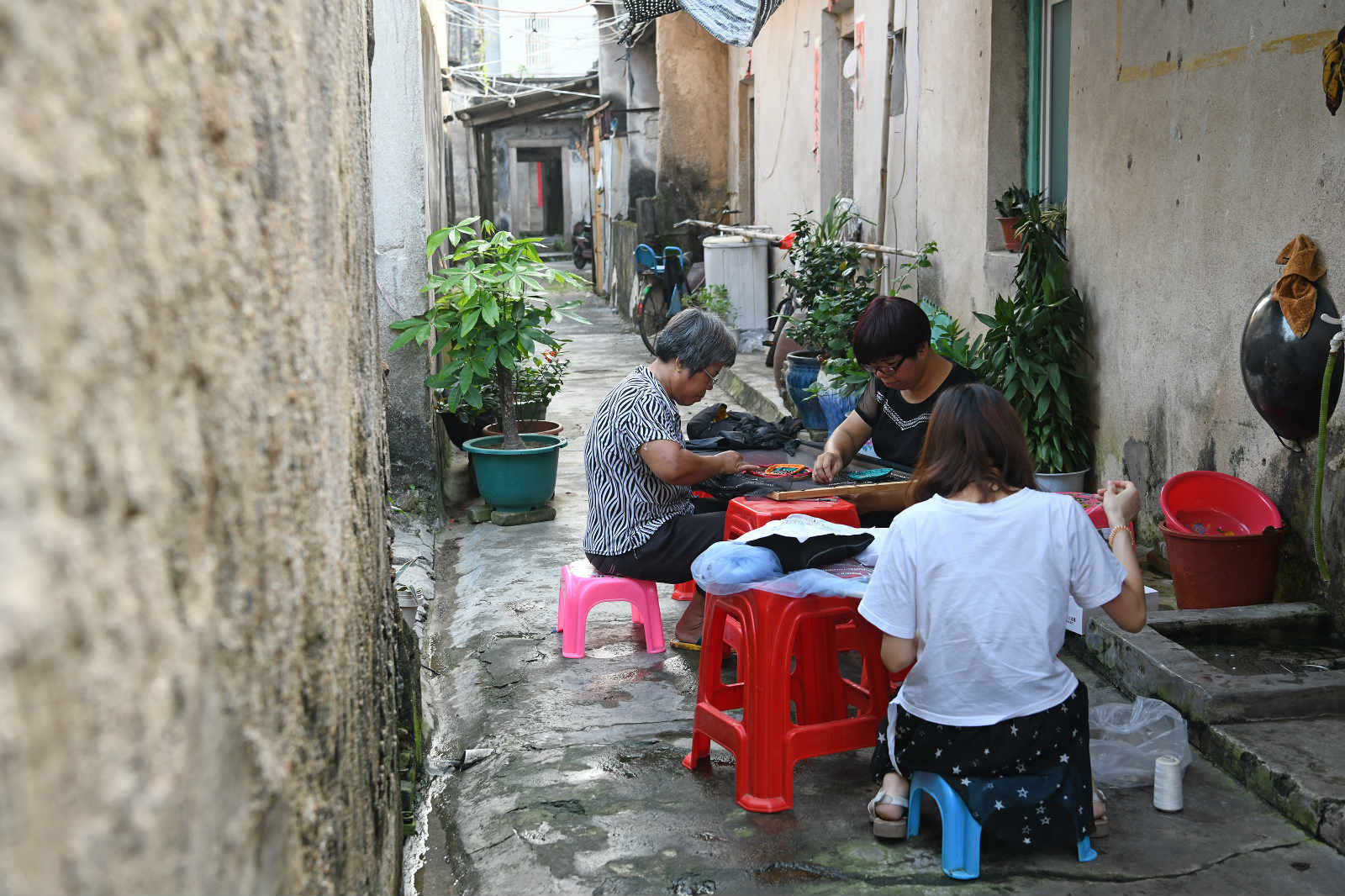 Wei Jingming (C) sews a piece of needlework with her daughter-in-law and cousin in Tahou Village of Linxi Township, Chaozhou, south China