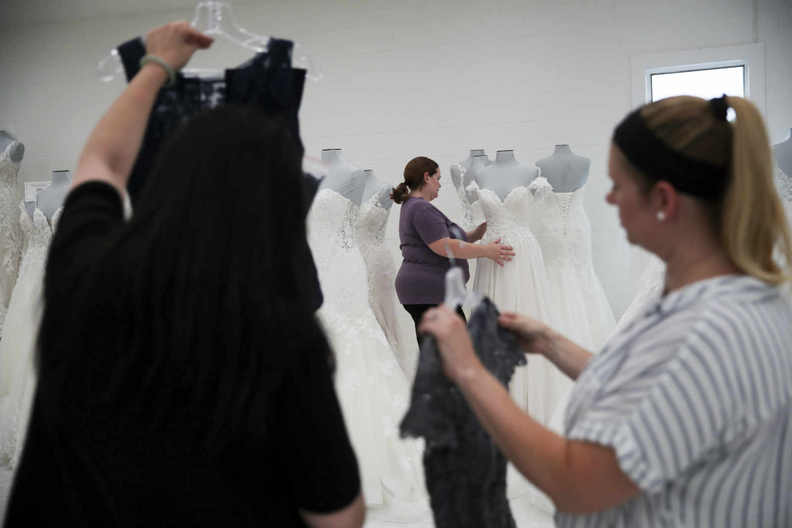 Workers settle bridal and prom dresses for display at U.S. brand Mon Cheri
